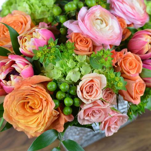 Orange and pink roses, pink ranunculus, tulips, green hydrangea and green hypericum berr