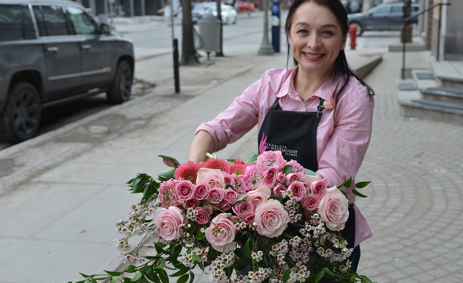 Westmount Florist employee holding a pink bouquet of flowers